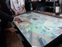 La table tactile de Taktus, avec des échantillons de parquet qui, une fois posés sur la table, appliquent ce qu'ils représentent à la simulation.